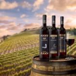 tre vini rossi sfondo vigneto